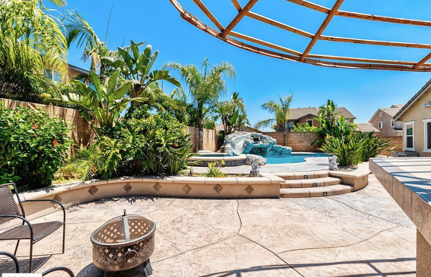 backyard with a rock pool with slide surrounded by lush tropical landscaping