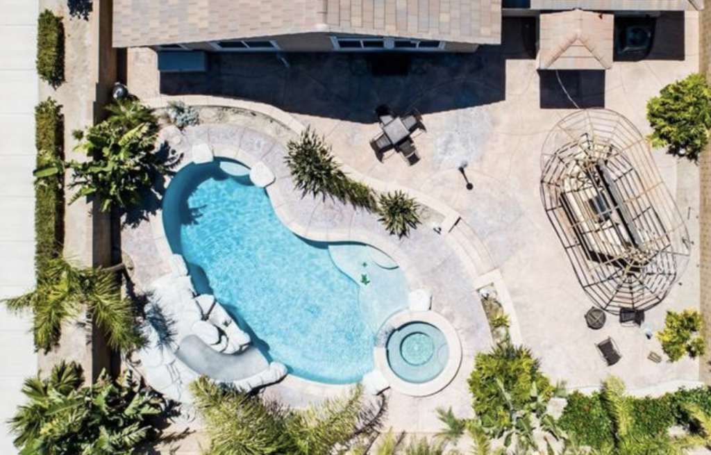 birds eye aerial view of a backyard with pool, outdoor kitchen, concrete and greenery