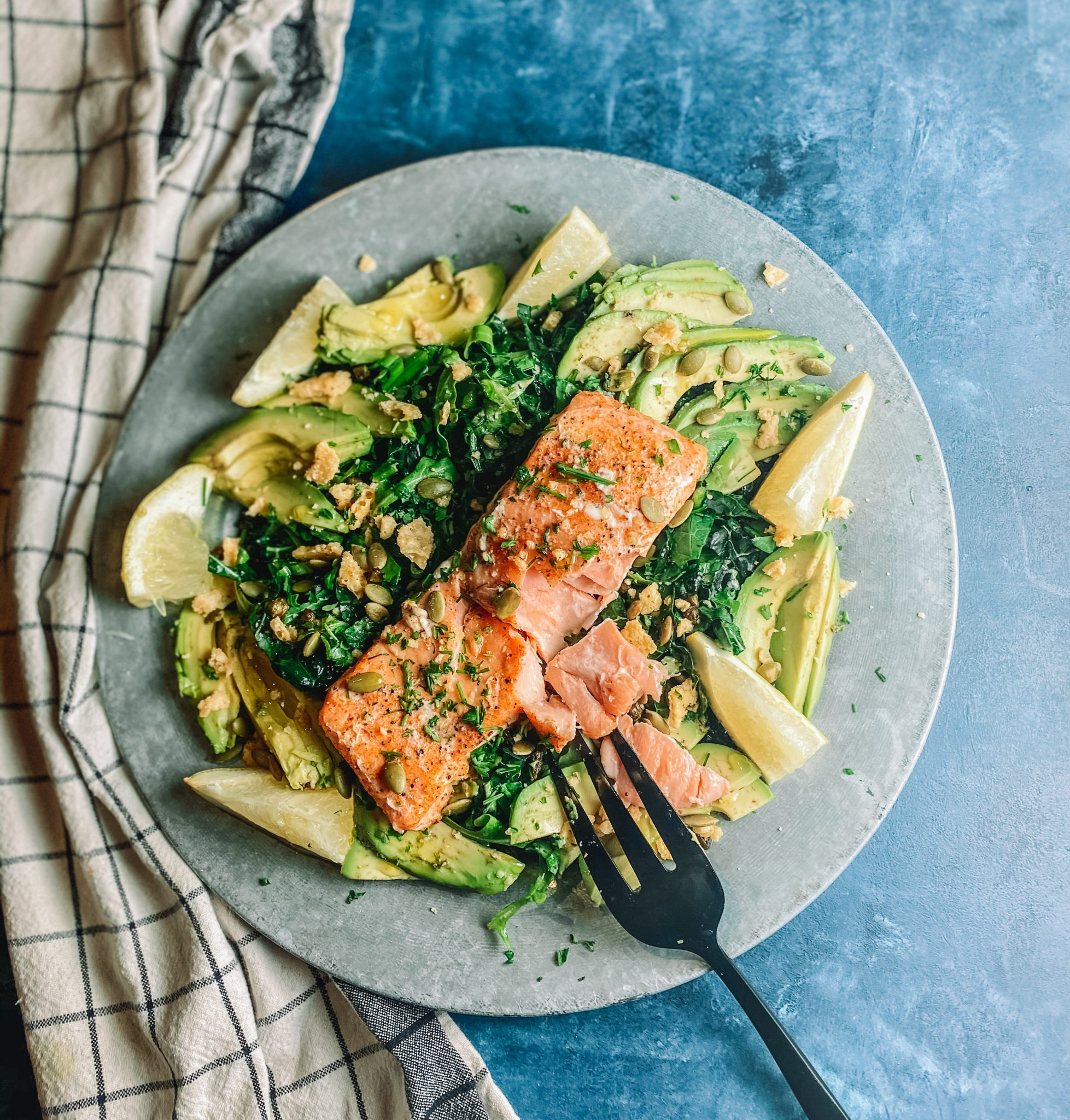 Salmon filet on a bed of greens and avocado, plated with a fork and a blue background.