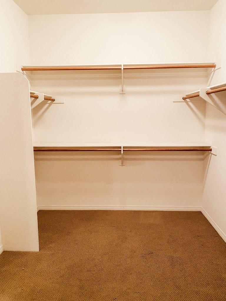 A closet with shelves and clothes hanging rods