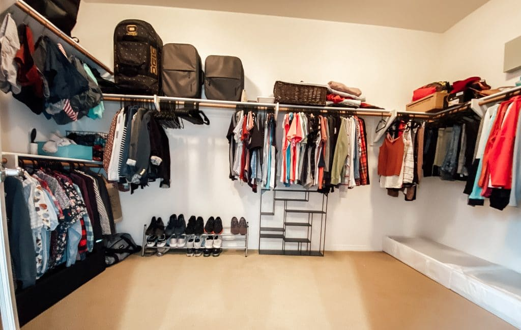closet with clothes hanging on rods and luggage on shelf above
