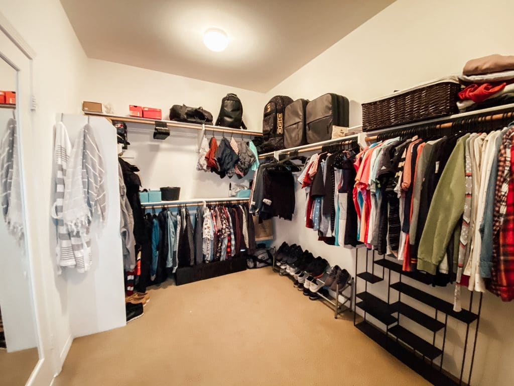 closet with hanging clothes and a light above shining down