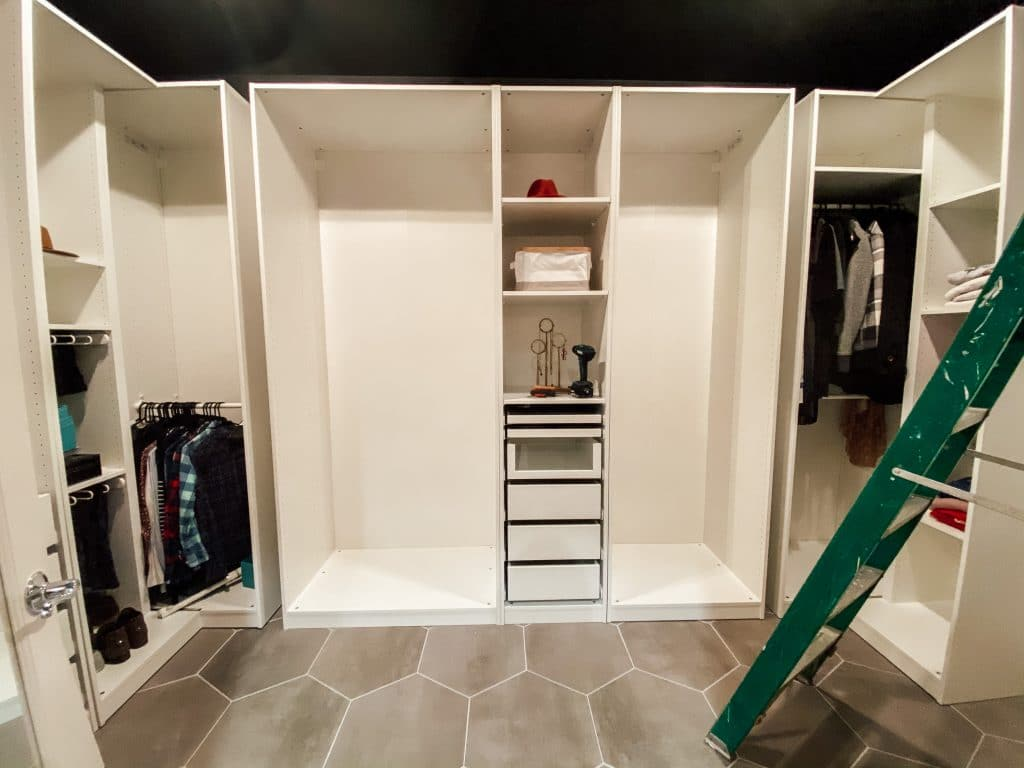 white closet components with some hanging clothes