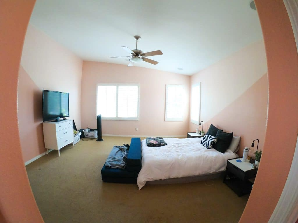 wide angle picture of owners suite with bed, nightstands, tv on dresser and ceiling fan