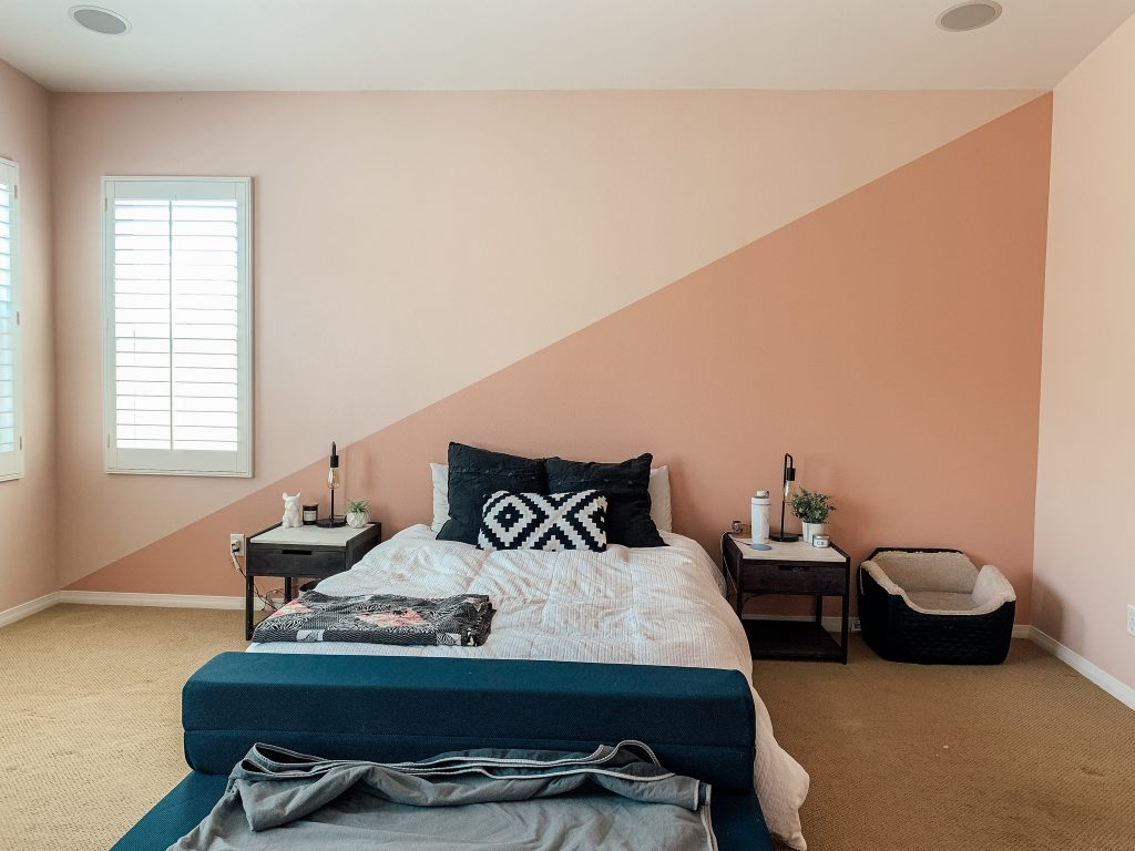 pink owners suite bedroom with a bed with a white bedspread and two nightstands