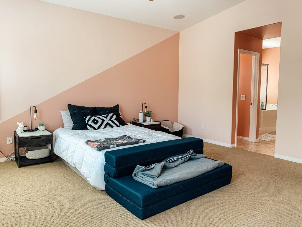 side angle of pink owners suite bedroom with bed with white bedspread and bath in distance through doorway