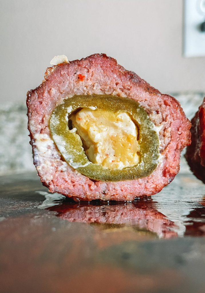 armadillo eggs - jalapeno stuffed with cream cheese and cheddar, wrapped in sausage and brushed with bbq sauce