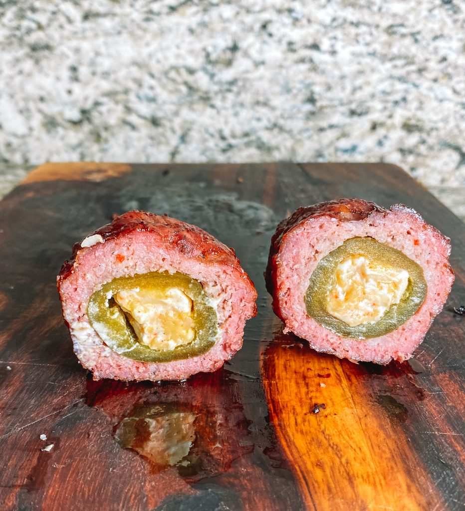 armadillo eggs made of stuffed jalapeno poppers wrapped in sausage