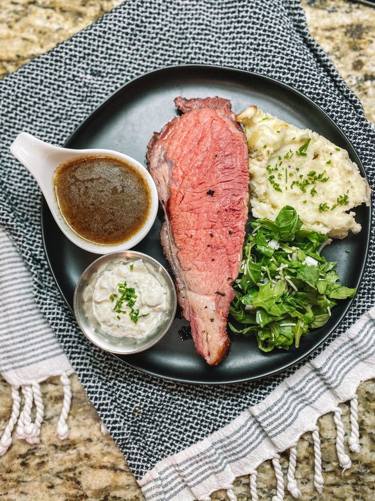 smoked prime rib being served on a black plate with mashed potatoes and salad