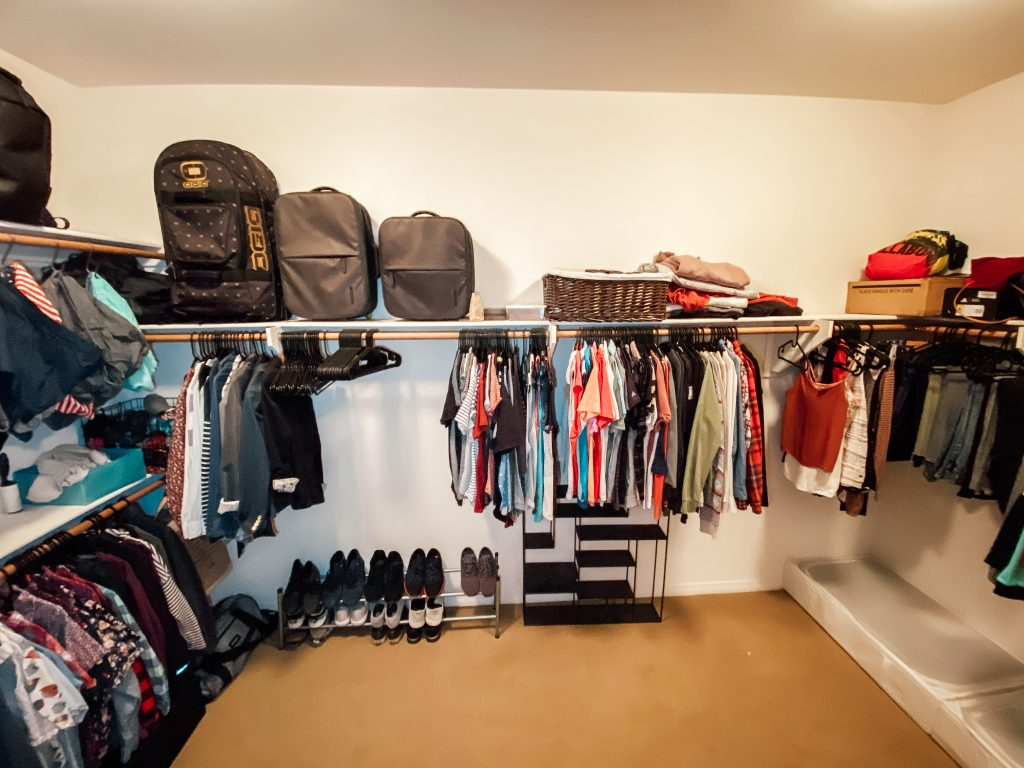 closet with hanging clothes rod, white walls, brown carpet