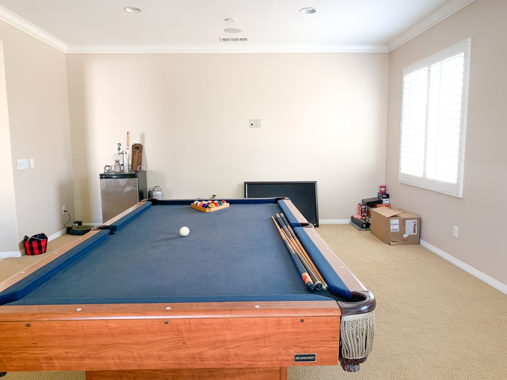 blue felt pool table in room with light beige walls