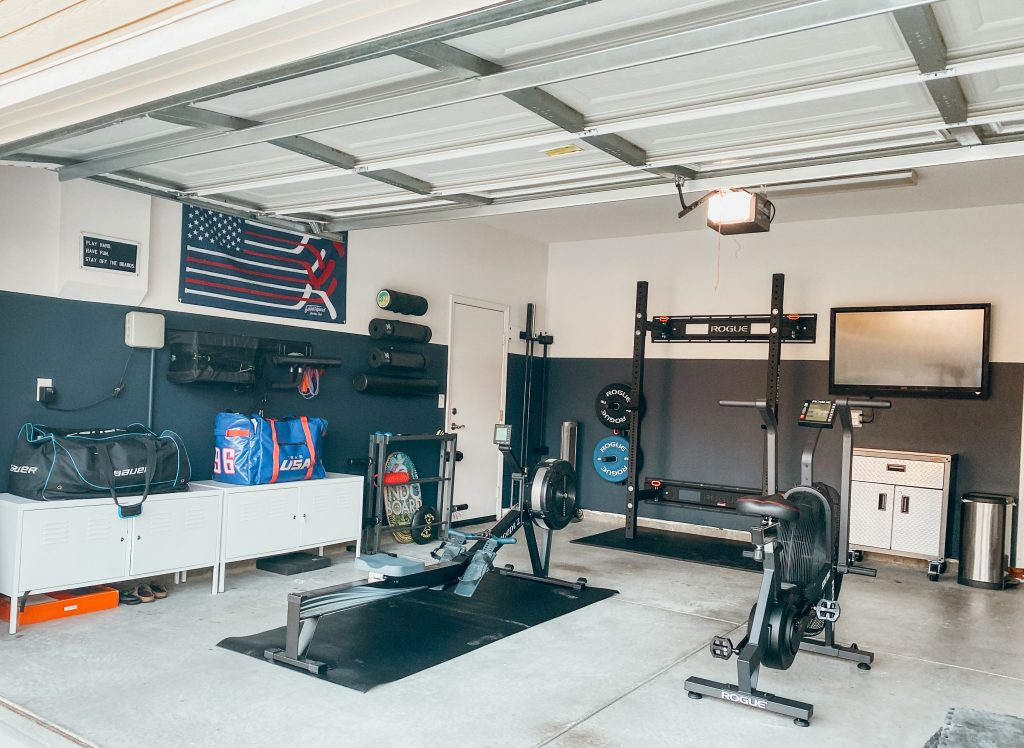 garage gym with exercise equipment like squat rack, rower, air bike