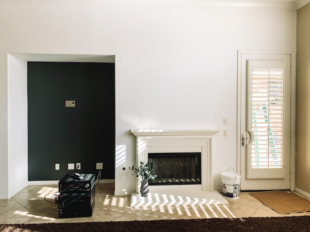 living room with white walls and black accent wall, fireplace