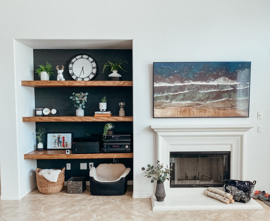wall with tv above fireplace, floating shelves to the left