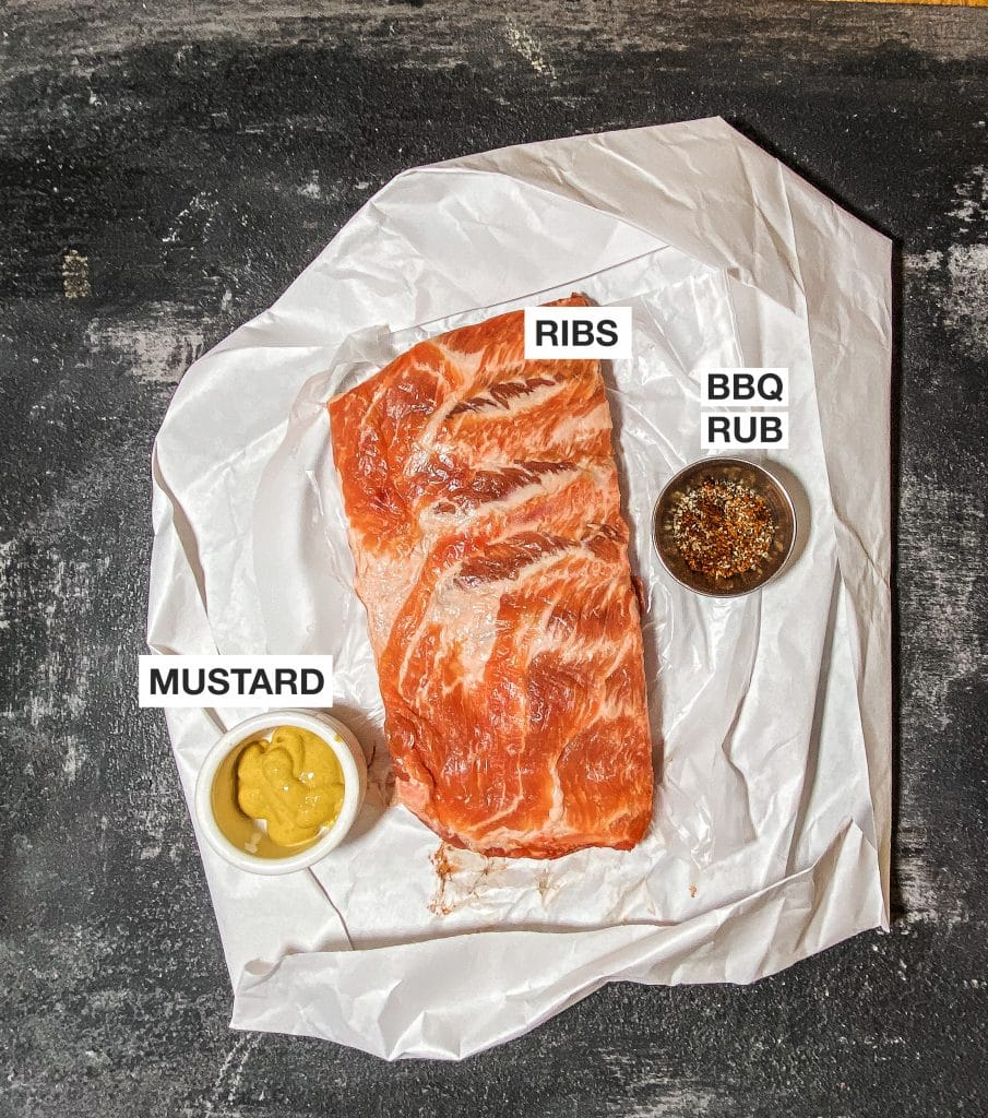 ribs, bbq rub and mustard on parchment paper non a black background