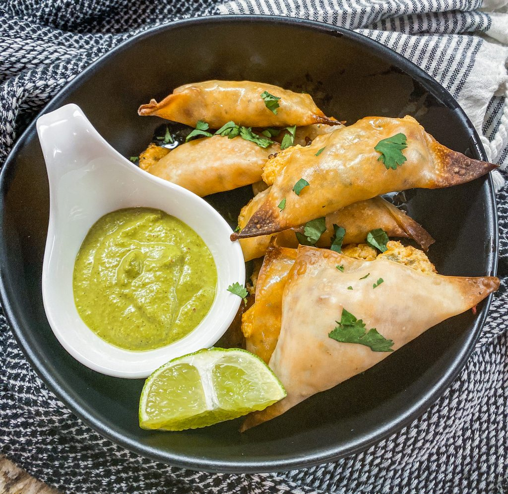 jalapeno popper wontons on a black plate with a lime and green sauce