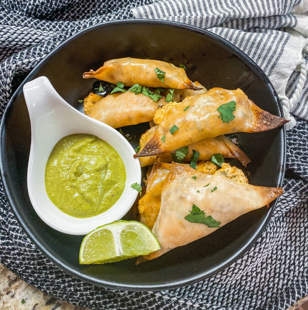 jalapeno popper wontons on a black plate with green dipping sauce and a lime