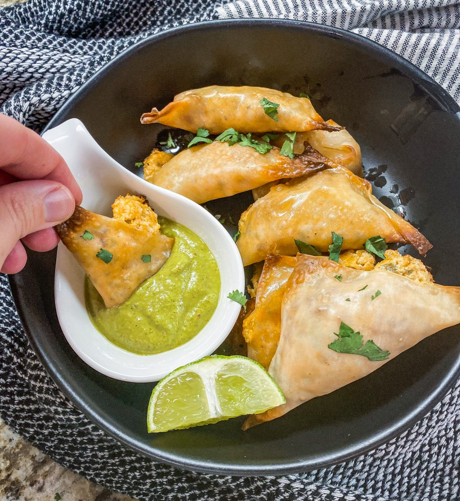 jalapeno popper wonton being dipped in green sauce